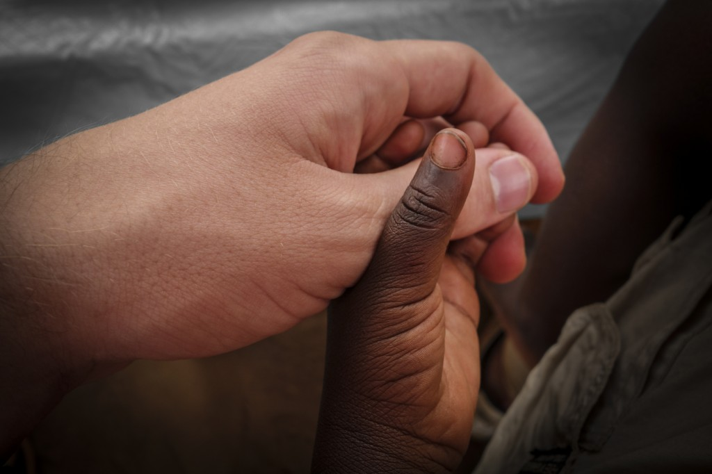 A black child and a white man hold hands.