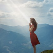 Beautiful woman in red dress standing on the stone and pray