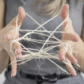 Woman making cats cradle out of twine