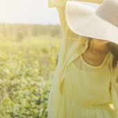 woman in sunny day with wide brim on summer nature.