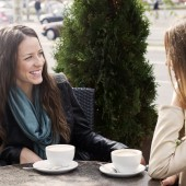 Two young women sitting in cafe and chatting outdoors.