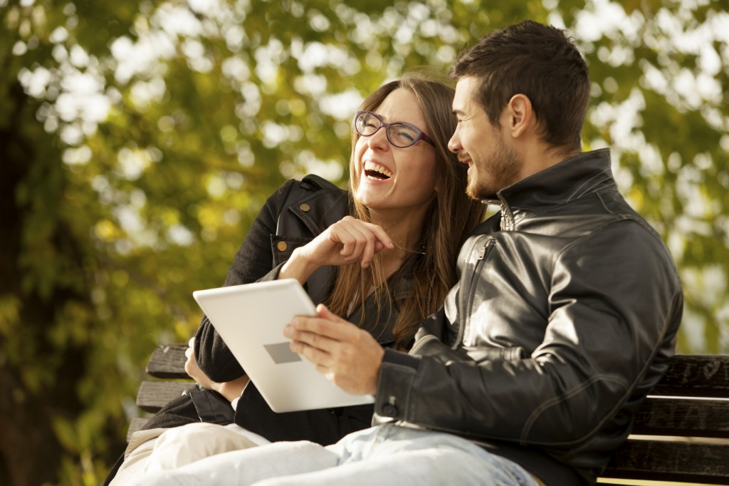 Happy Couple Using Tablet Computer Outdoor