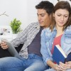Young couple reading and using a tablet on a couch