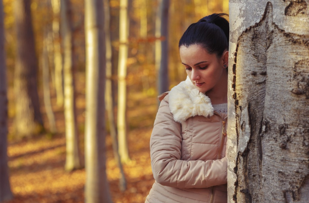 Sad woman in forest while autumn season