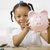 Responsible girl putting money into piggy bank for future saving