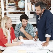 Three architects around a table looking at sketches and discussing designs