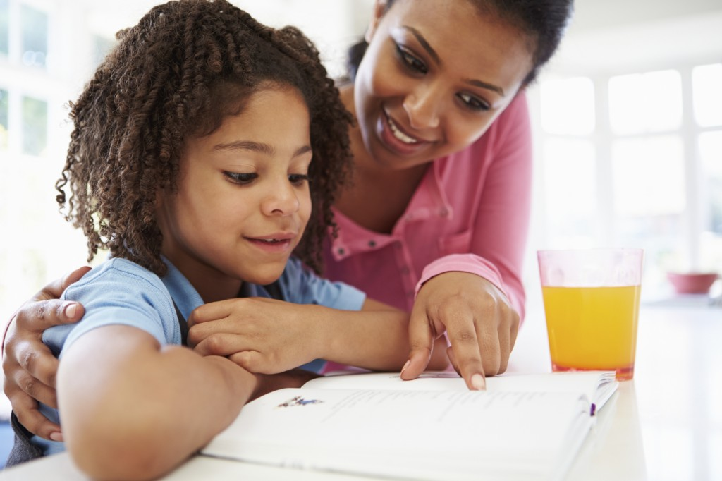 Mother Helping Daughter With Homework In Kitchen With Orange Juice