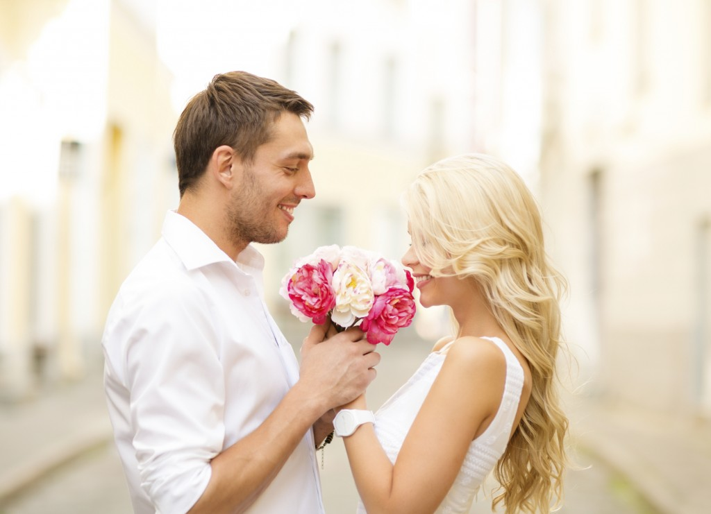 couple with bouquet of flowers in the city