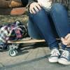 Legs of a girl sitting on a skateboard