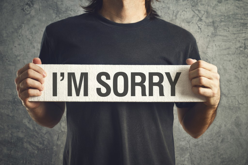 Man holding I am sorry message on white board.