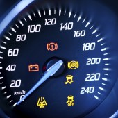 Fragment of instrument panel of car speedometer, tachometer with visible symbols of instrument cluster, with warning lamps illuminated.