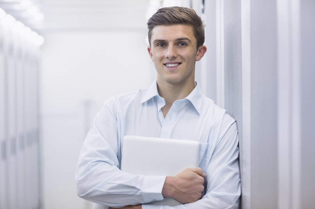Portrait of a smiling technician holding a laptop and leaning against a tower in a large data center