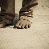 Shot of a Cambodian child's feet on the pavement.