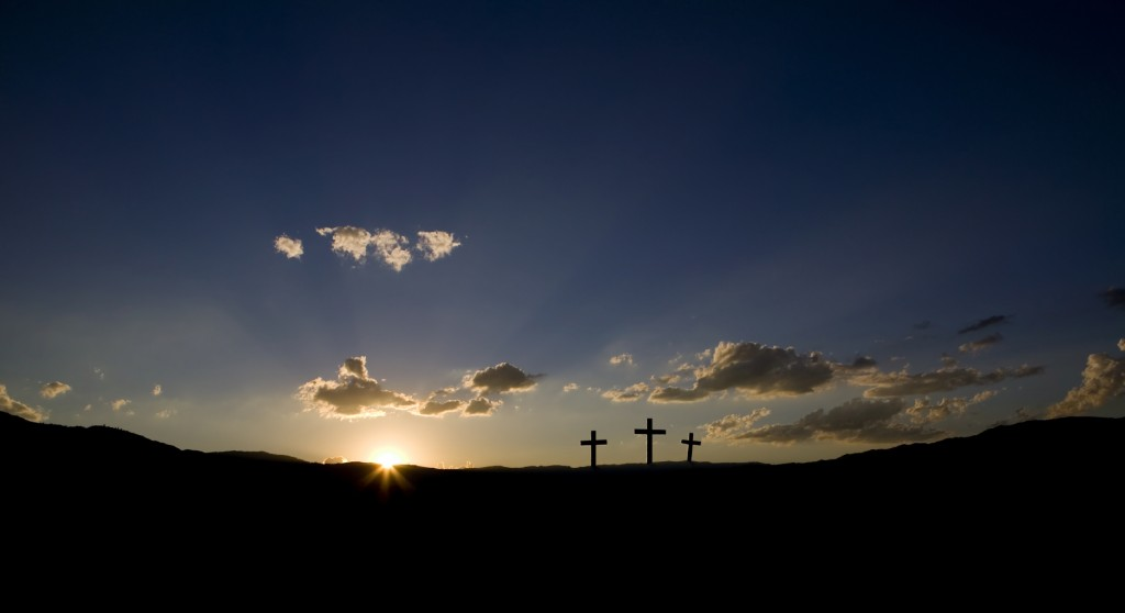 Sun rising on three Christian crosses.