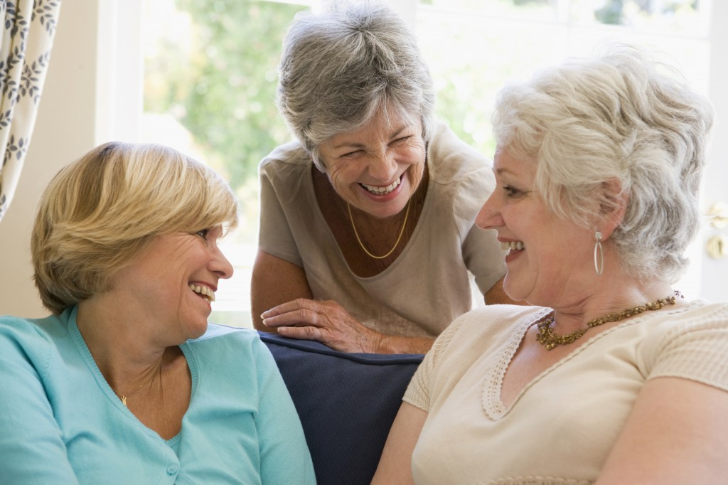 Three women in living room talking and smiling
