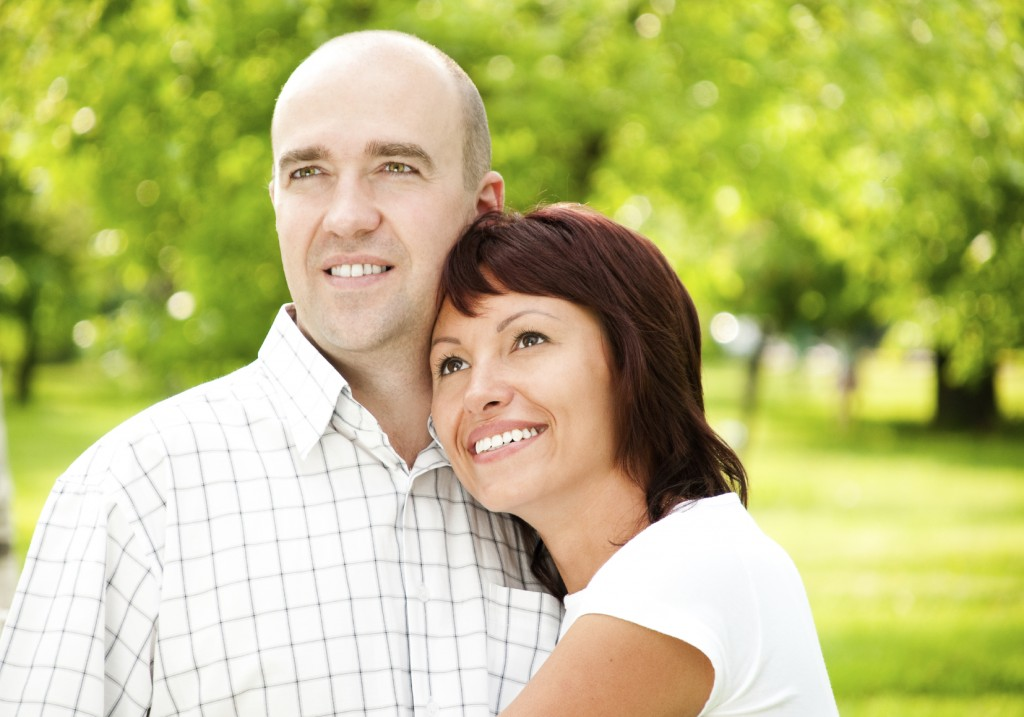 couple of husband and wife in park, both smiling and looking away from camera