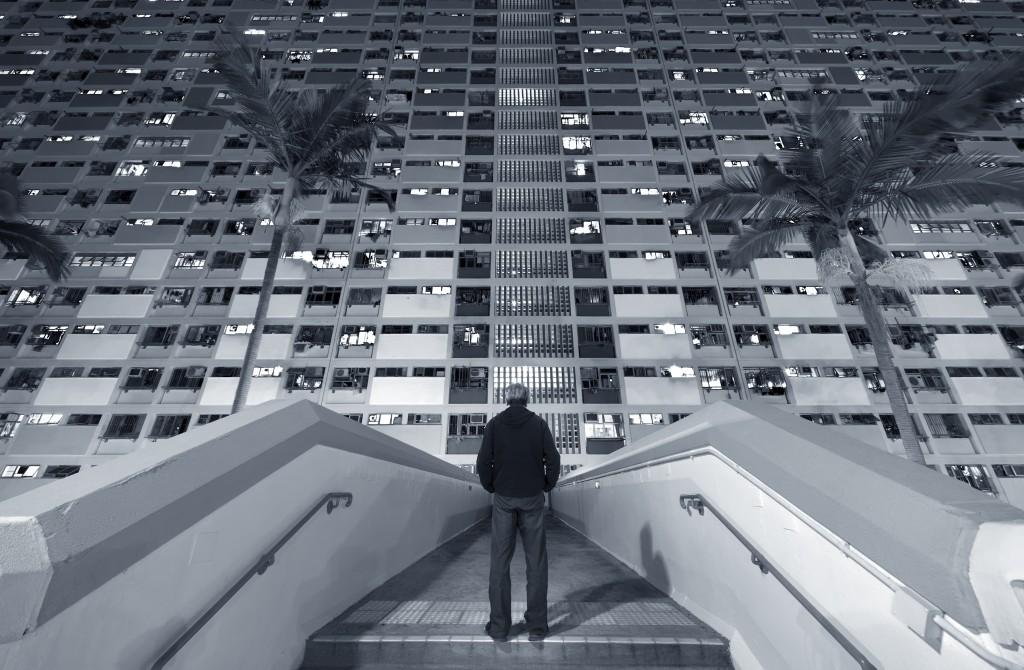 A man stand in front of a crowded residential building