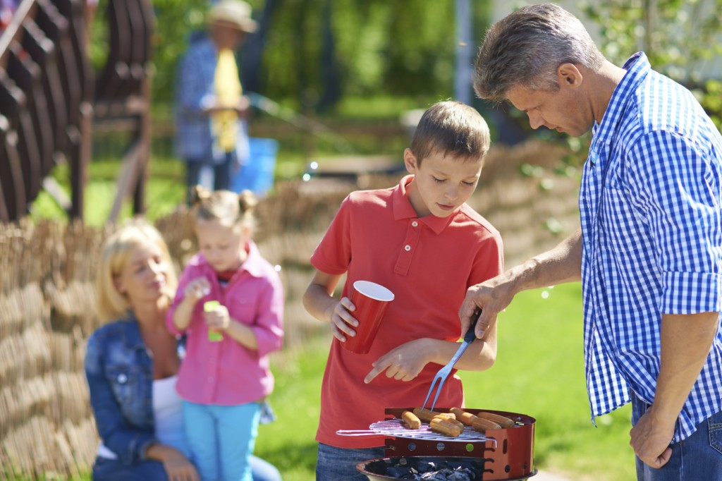 Father and son frying sausages at their gathering with family