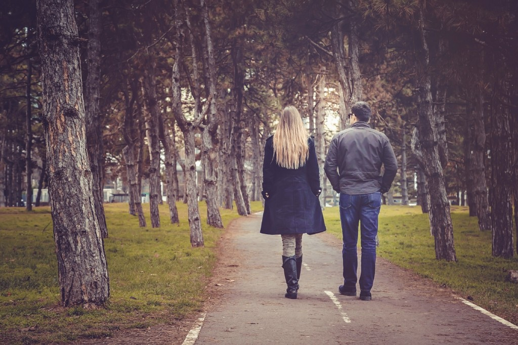 rear view of couple walking through autumn city park