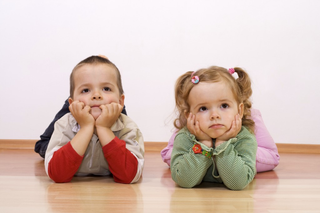 Two kids bored, looking at something - laying on the floor
