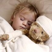 boy and teddybear in bed