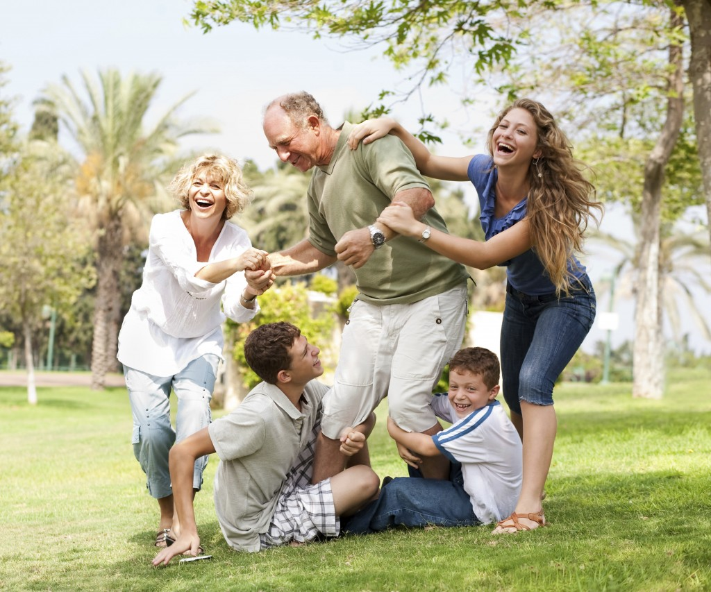 Family holding back grandfather and having fun