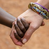 A black child and a white woman hold hands.