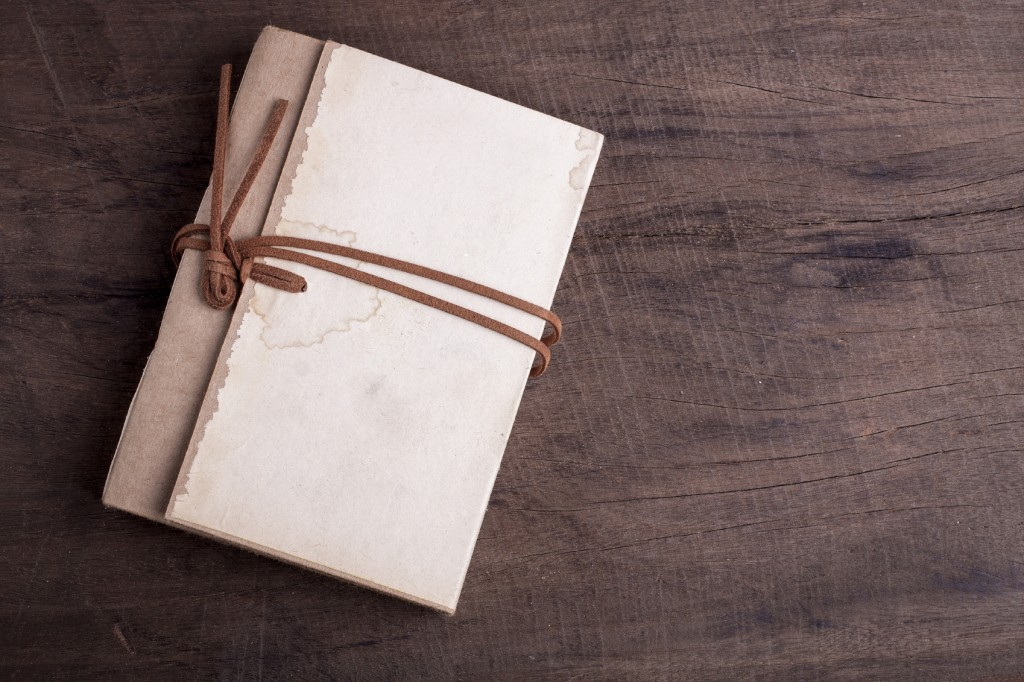 Old notebooks Was strangled with a leather strap on wooden background