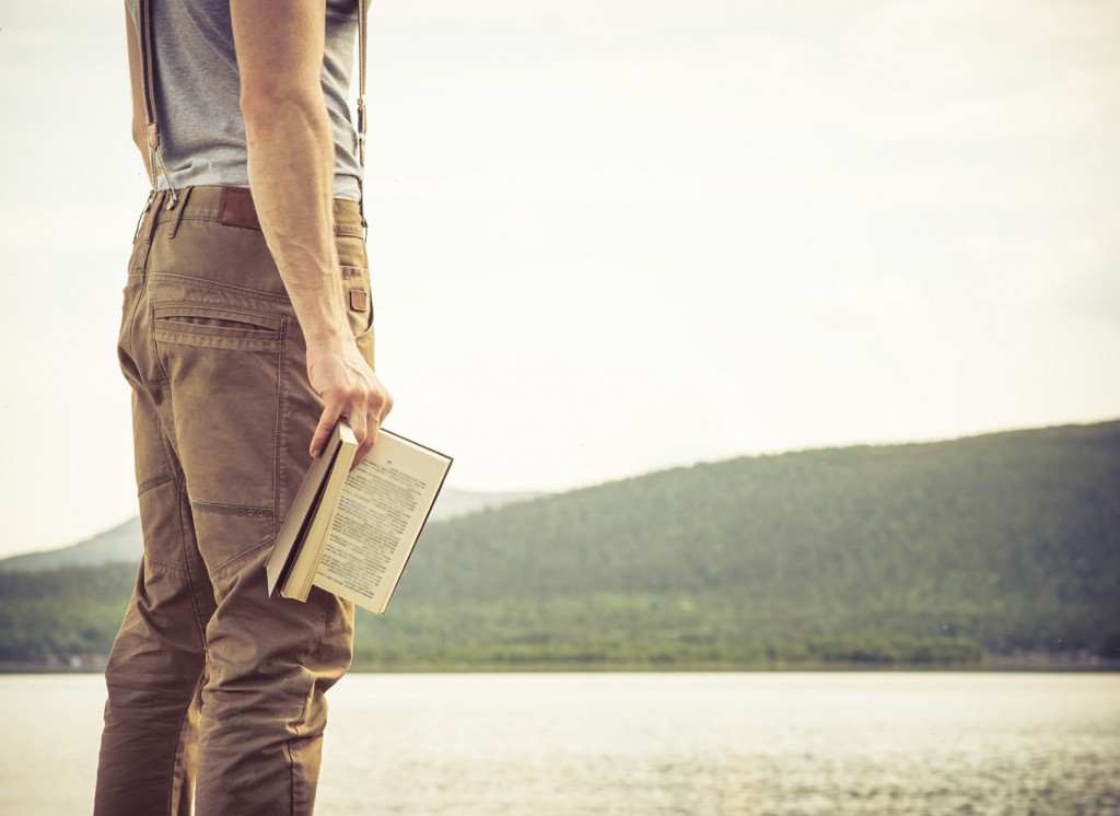 Young Man with book outdoor lake on background