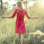 Woman walking in the sun in a red dress