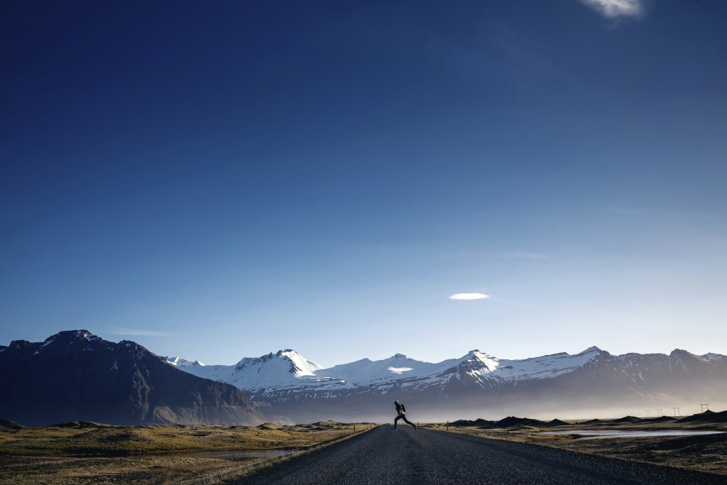 Man jumping on Winding mountain road next to Hvalfjordur fiord in Iceland