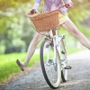 Woman riding bicycle with her legs in the air