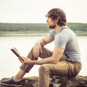 Young Man reading book outdoor Summer vacations Lifestyle