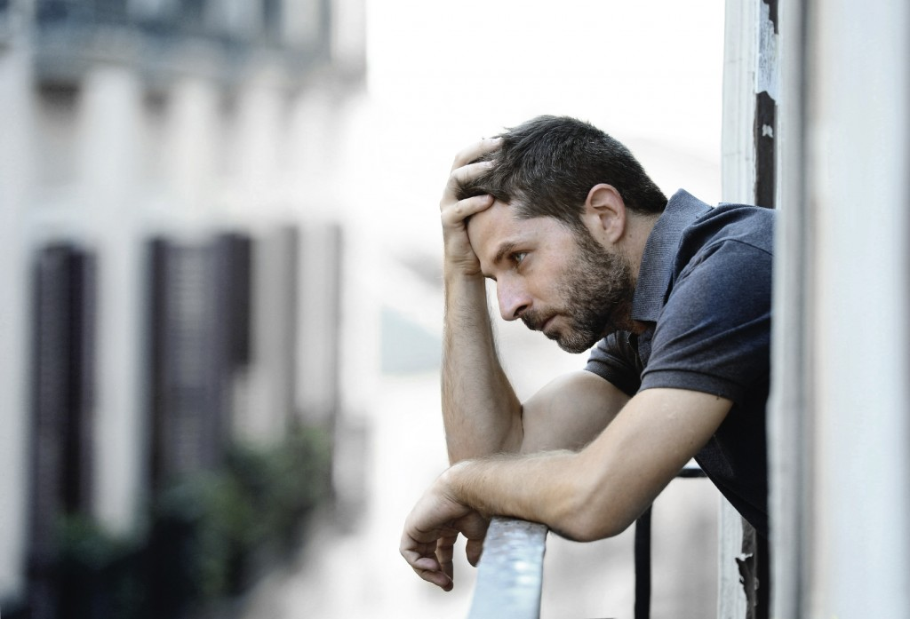 young man at balcony in depression suffering emotional crisis and grief