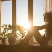 Woman sitting by window watching the sun rise