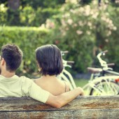 Couple in love hugging each on a bench with bikes