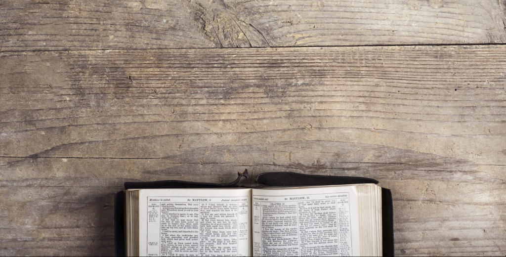 Opened bible on a wooden desk background.