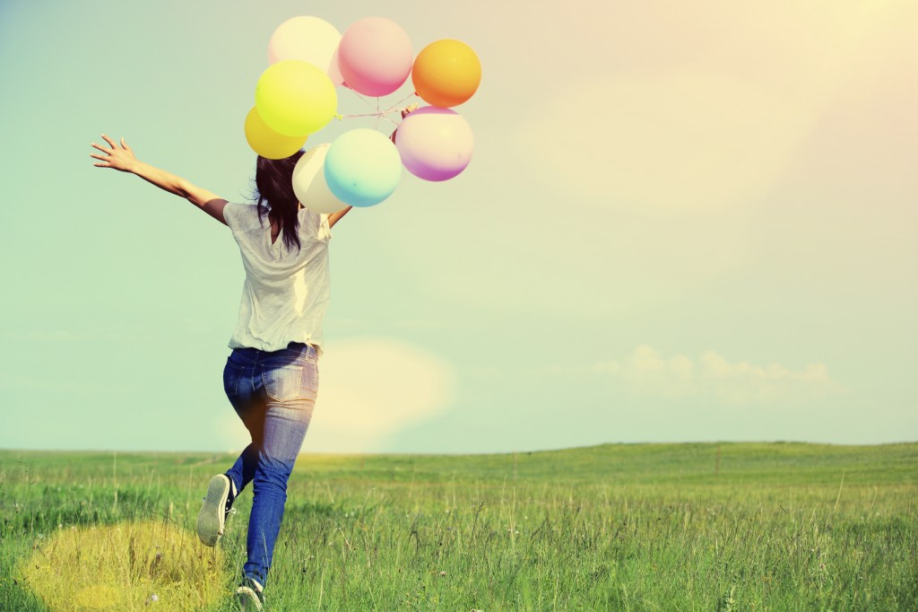 young asian woman running and jumping with colored balloon