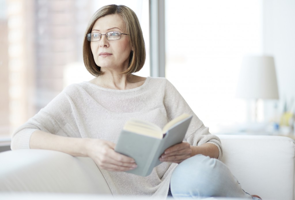 Charming mid age lady enjoying being at home and reading