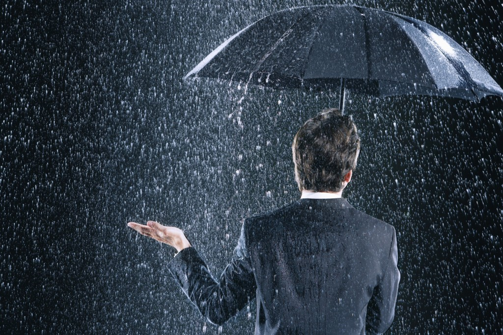 Rear View Of Businessman Under Umbrella In Rain