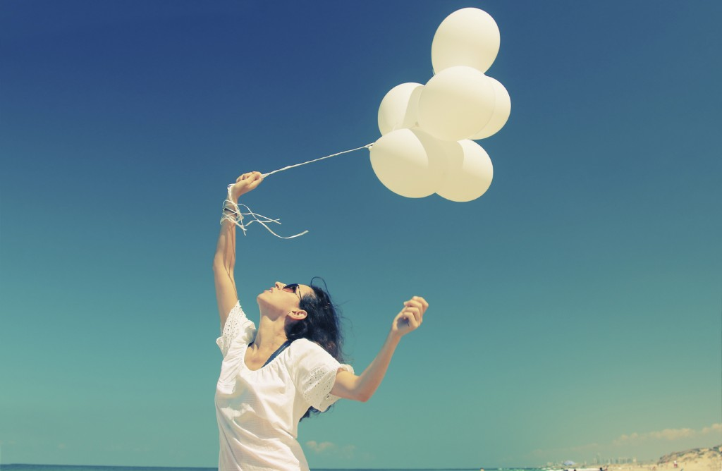 woman with white balloons on seaside