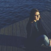 Portrait of a young woman sitting on a pier and admitting beautiful view