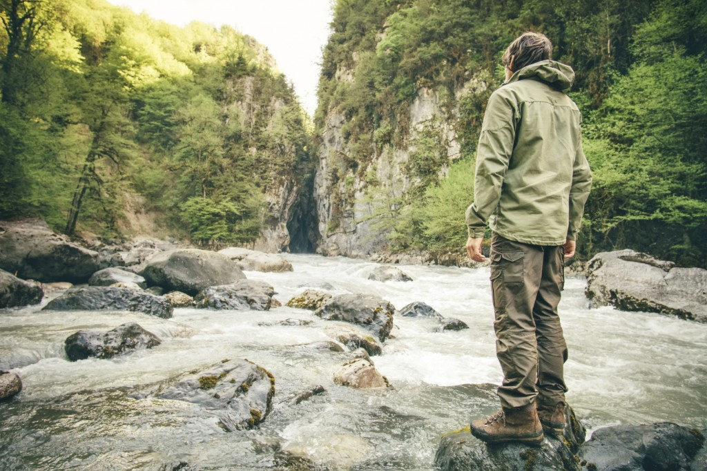 Young Man hiking outdoor Lifestyle Travel survival concept river and rocky mountains on background