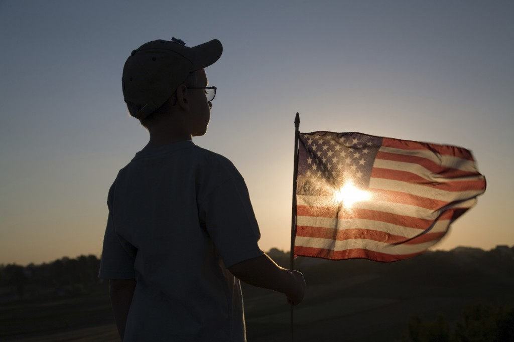 boy holding American flag watching the sun set.