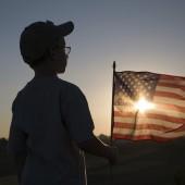 boy holding American flag watching the sun set.