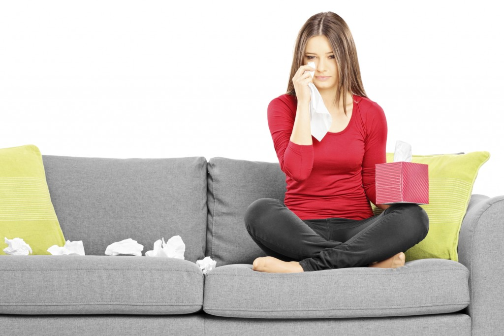 sad young female sitting on a couch and wiping her eyes from cry