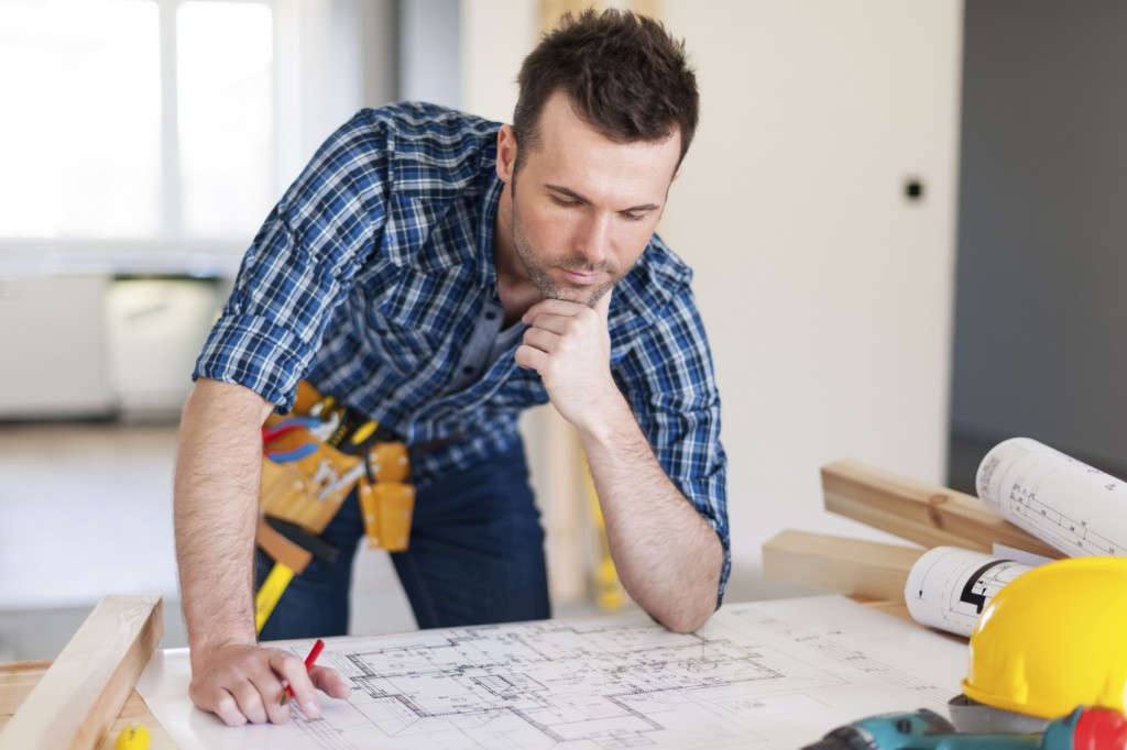 Building contractor bending over home plans