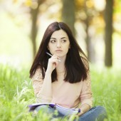 Brunette girl with notebook in the park.