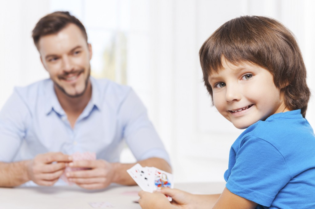 Enjoying free time together. Happy father and son playing cards and smiling