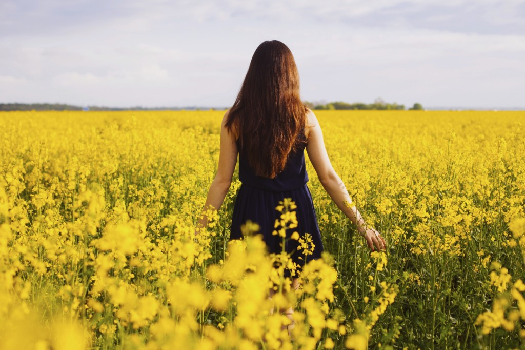 Girl enjoying rapeseed blooming on yellow meadow
